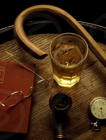 Scotch Whiskey glass with wooden barrel cane pipe pocket watch book and reading glasses. photo