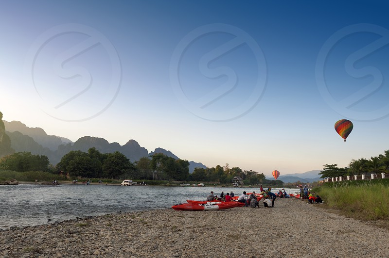 Hot air balloons flying over Nam Song River and tourist kayaks in Vang Vieng popular resort town in Lao PDR photo