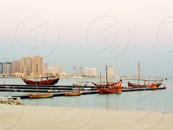five assorted boats on body of water near wooden dock during daytime photo