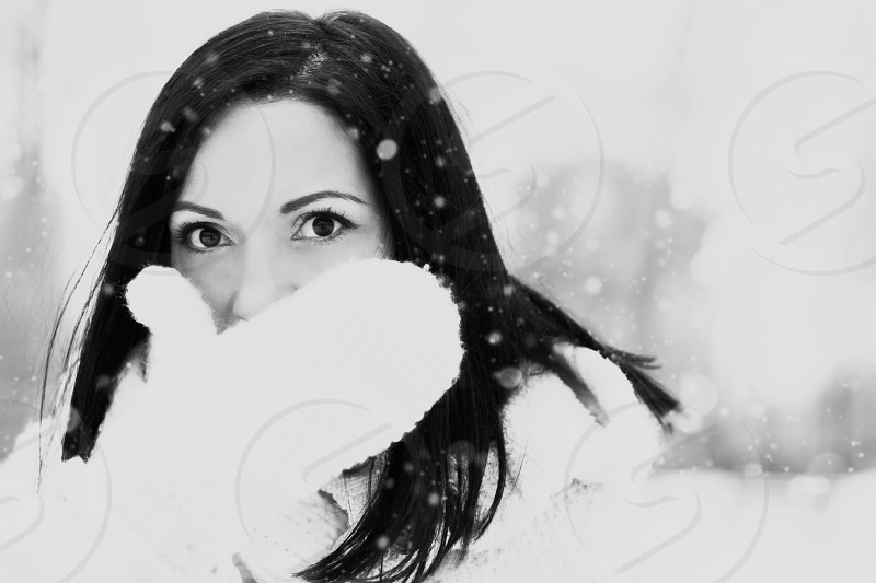 Woman with black hair with white knitwear gloves covering her face while snowing monochrome effect. photo