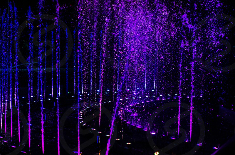 A purple and blue fountain at night. photo