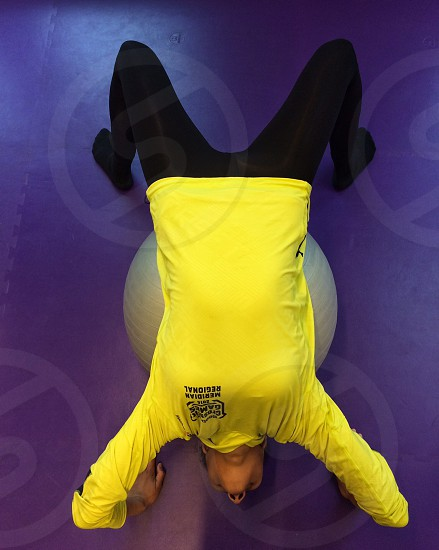 person wearing yellow sweater and black pants playing on white stability ball photo