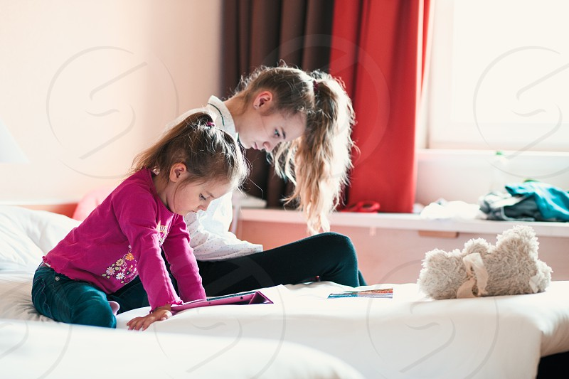 Teenage girl using mobile phone together with her little sister watching animated movie on tablet both girls sitting in bed in bedroom photo