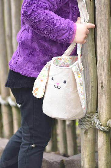 Bunny Easter basket bag child black pants purple coat wood fence photo