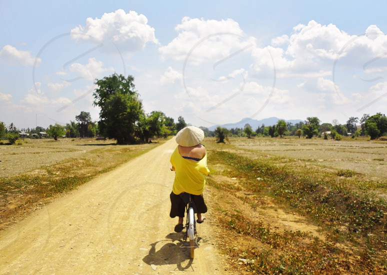 person in yellow shirt and black pants riding a bike on brown dirt road between grass fields under cloudy sky during daytime photo
