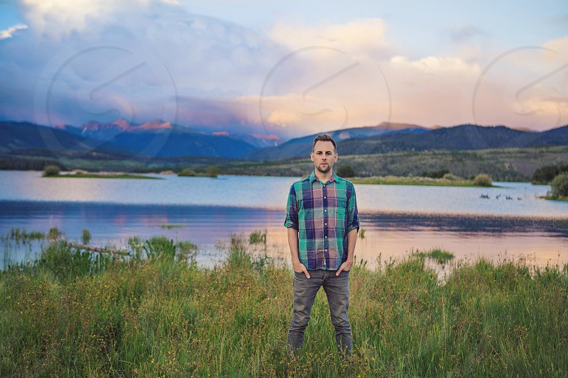 young man mid thirties plaid shirt hipster cool standing in beautiful mountains mountains man peak clouds rain sun set lake water grass natural nature organic healthy artsy dream photo