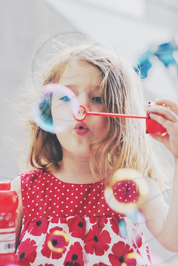 a young girl blowing bubbles in a red flower shirt photo