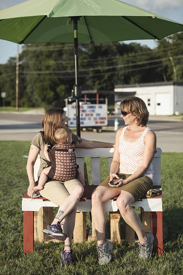 Two ladies (one with a baby strapped to her) talk on a park bench.  photo