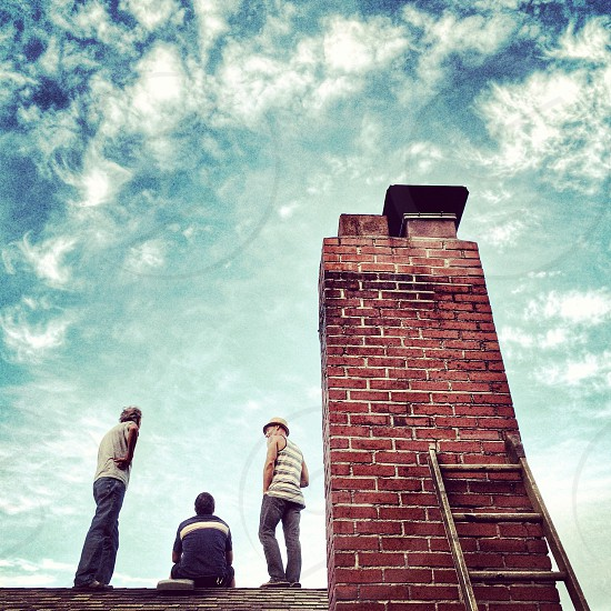 2 men standing and 1 man sitting on brown bricked roof photo