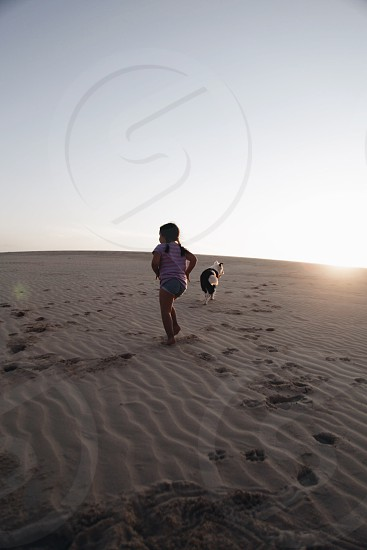 girl running on desert with dog during sunset photo
