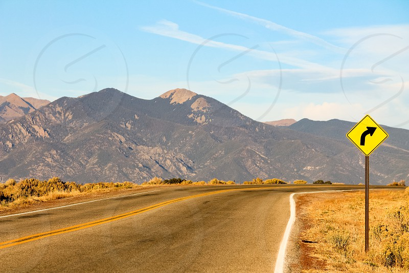 A sign warns of a right curve ahead on a mountain road in Colorado near Aspen photo