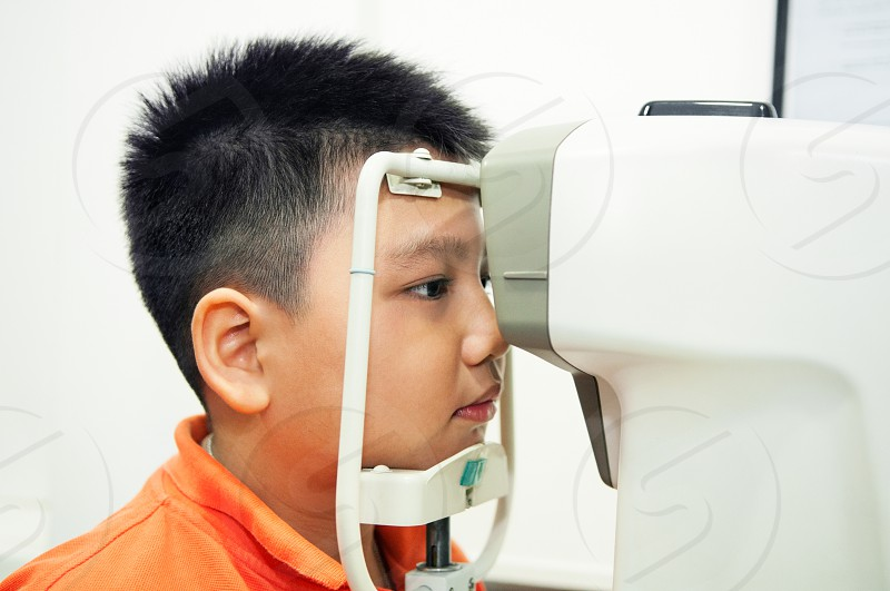 Portrait of an Asian boy undergoing an eye examination with slit lamp microscope. photo