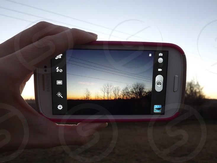 Android phone taking a photo of a sunrise. photo