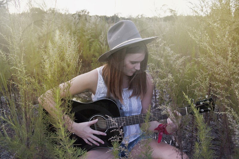 woman in white tank top playing guitar surrounded of green grass during day photo