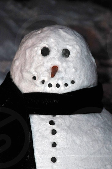 Traditional snowman wearing a scarf photo