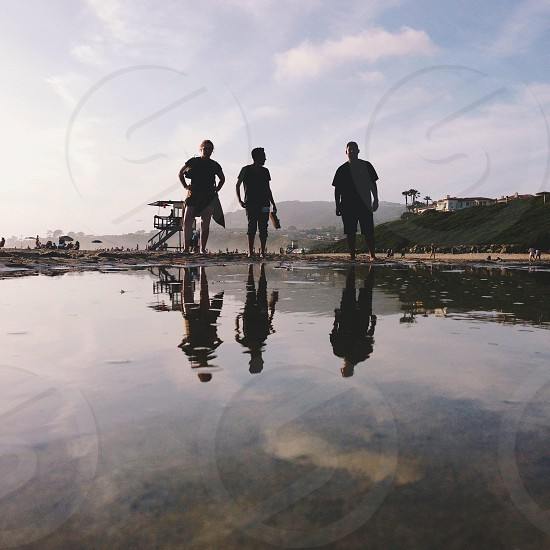 3 human silhouettes standing on a water photo