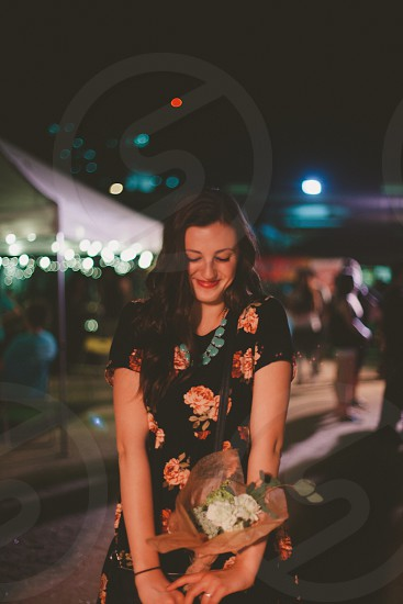 woman in black and orange floral dress holding a bouquet of flowers photo