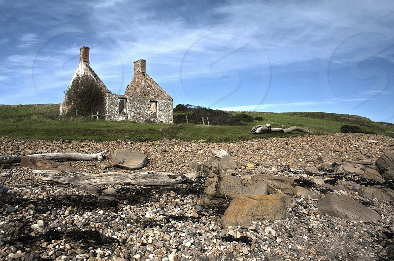 Stone ruins of a cottage on the Scottish coast under a blue sky with wispy white clouds. photo