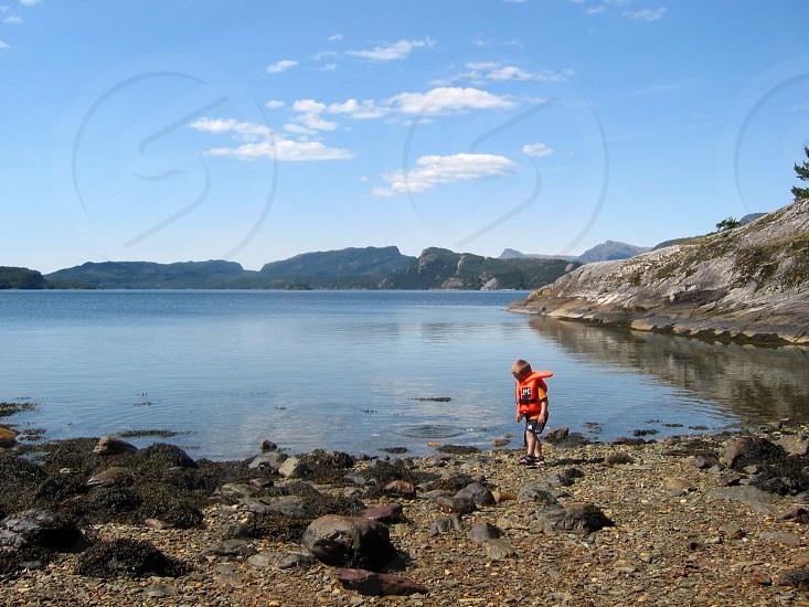 boy in orange life jacket walking on sea rocking shore photo
