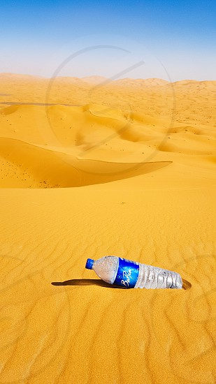 Litter in the desert plastic bottle on the sand in the Sahara desert. photo