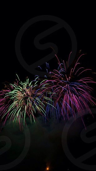 purple and green fireworks photo
