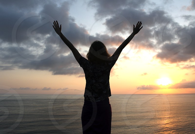Holiday woman girl young weekend winner freedom view victory vacation travel sunset sunrise sunlight sun summer success happy sky silhouette sea ocean rest relax raised nature life lifestyle landscape joy horizon hand enjoyment energy beauty beautiful beach arms background photo