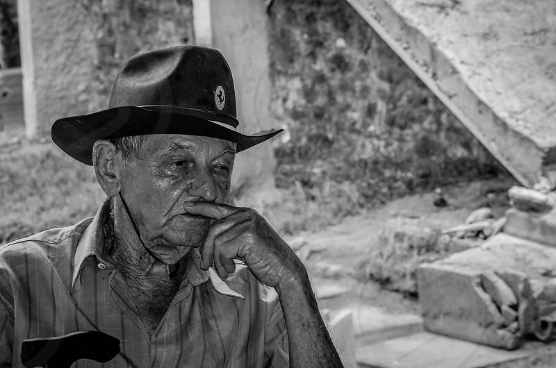 man wearing black hat sitting photo