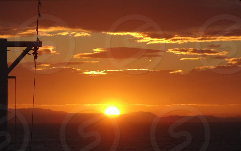 sun setting over mountain range beneath white orange clouds photo