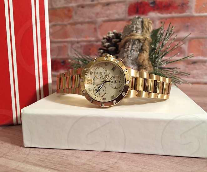 gold links bracelet round chronograph watch above white with tree branch patched case beside red and white stripe case on wooden table photo