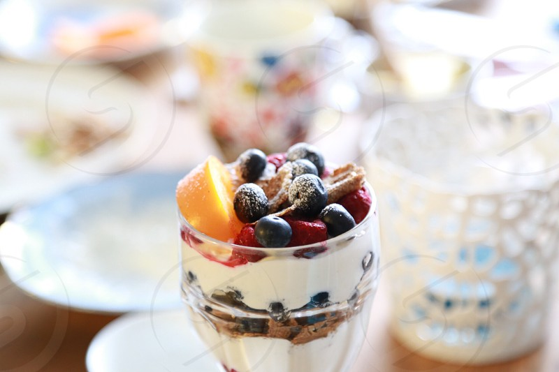 Breakfast  table cottage cheese berries blueberries cup oat persimmon  layers raspberries  photo