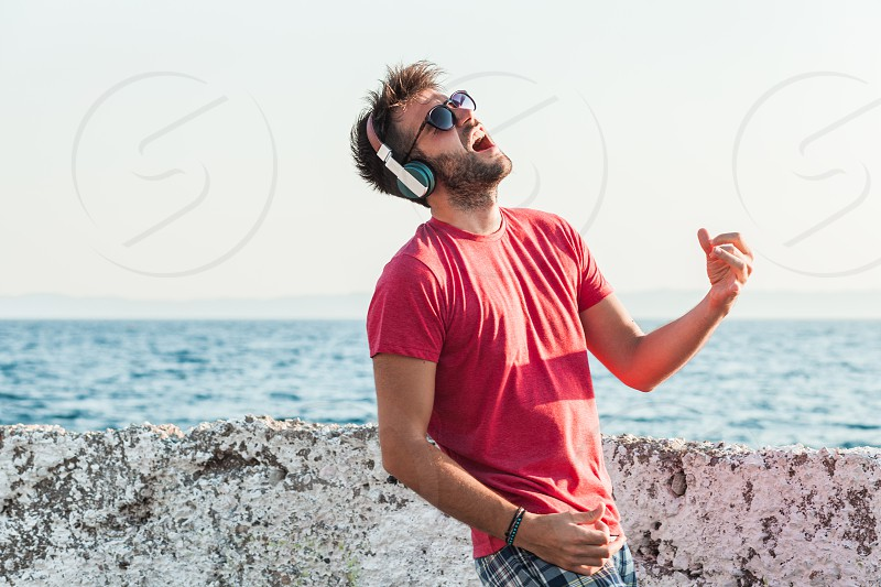 Young man listening to the music on headphones playing imaginary guitar by the sea photo
