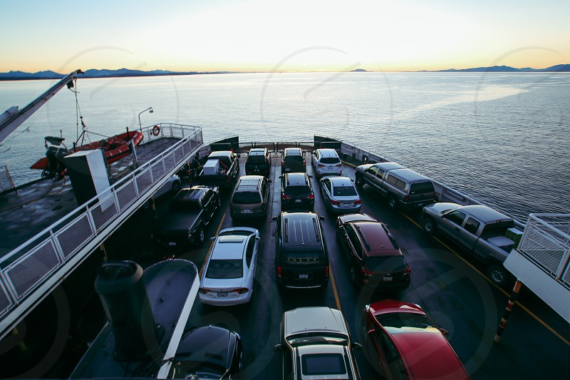 vehicles on the ship on water below bright sky during daytime photo
