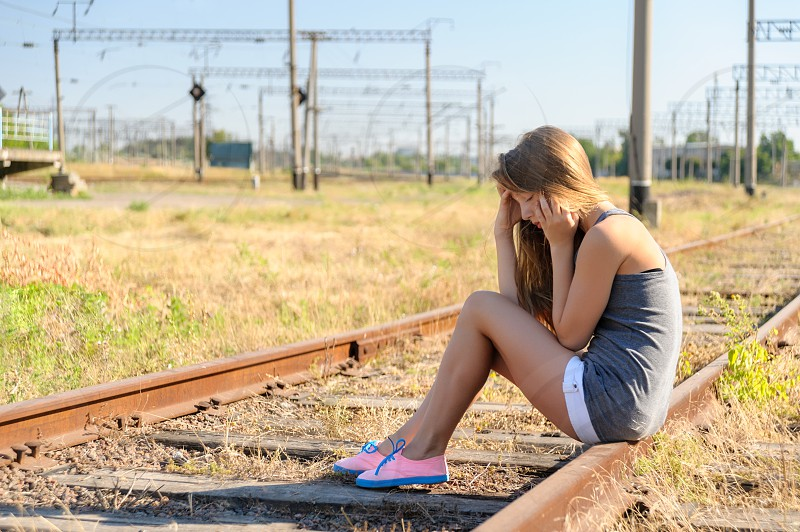 Sad girl teenager sitting on rusty rail track outside the town. Escape to be alone photo