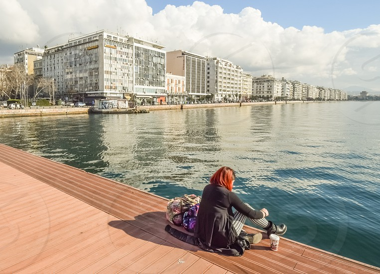 Young Woman With Her Baggage Sitting Alone At The Dock Drinking Coffee And Enjoying The View photo