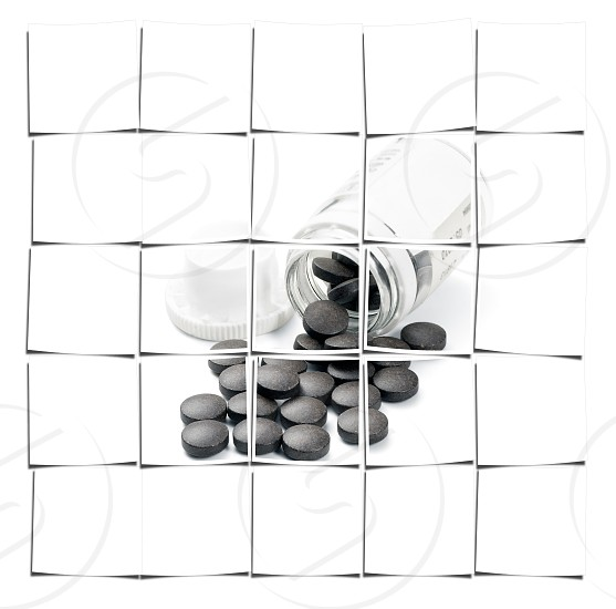 brown pills spilled from glass bottle on white background photo