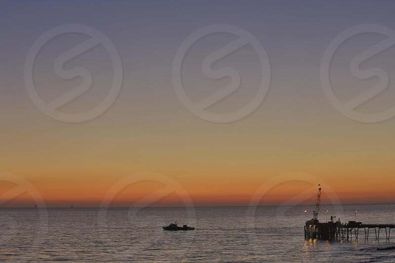 Boat leaving the oil docks during sunset photo