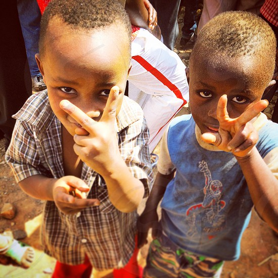 two male children with their hands forming peace sign as the stand on a road during daytime photo