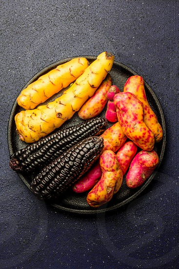 Peruvian raw ingredients for cooking black corn and sweet potatoes photo