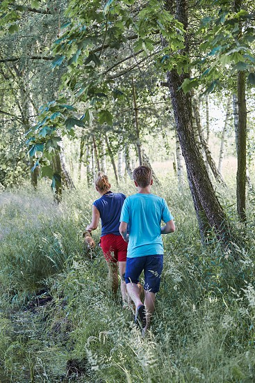 Mother and her son walking along a path among the trees close to nature during summer vacations. Candid people real moments authentic situations photo