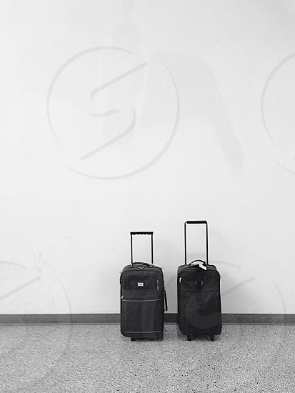 black luggage by wall photo