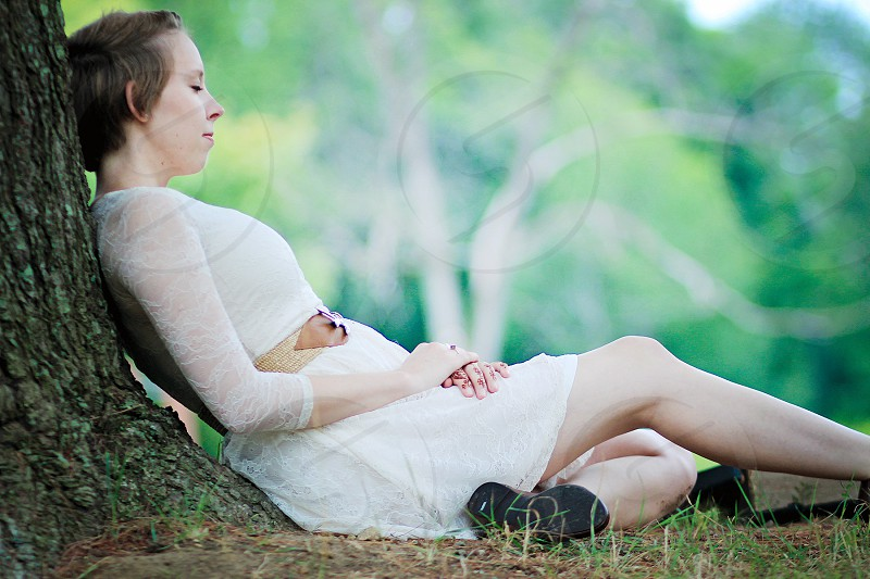 woman in white dress sitting against a tree trunk photo