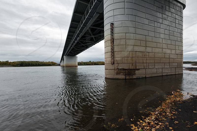 Bottom view of modern automobile bridge over Kamchatka River - largest longest and most flooded river on Kamchatka Peninsula. View of bridge on cloudy day. Eurasia Russian Far East Kamchatka Region photo