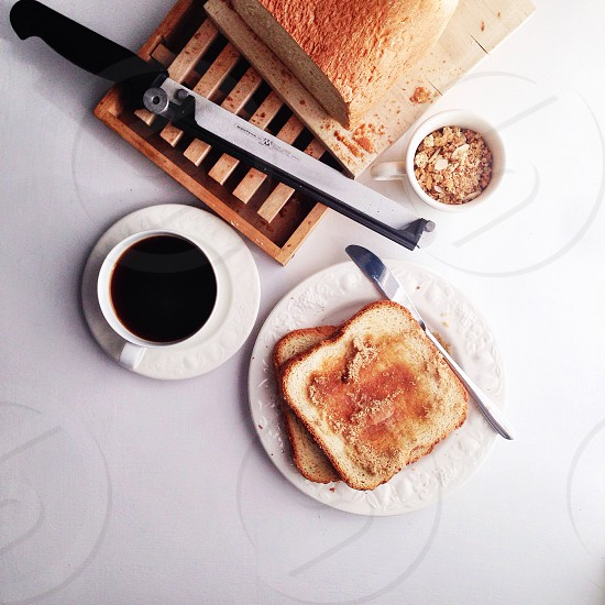 sliced breads and stainless steel dining knife on white saucer photo