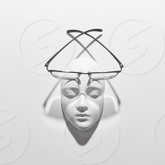 Gypsum face sculpture with elegant glasses with long crossing shadows on a white background copy space. Top view. Concept healthy lifestyle. photo