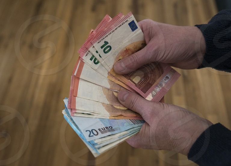 woman counting euro banknotes from ten and twenty with wooden table as background from Holland photo