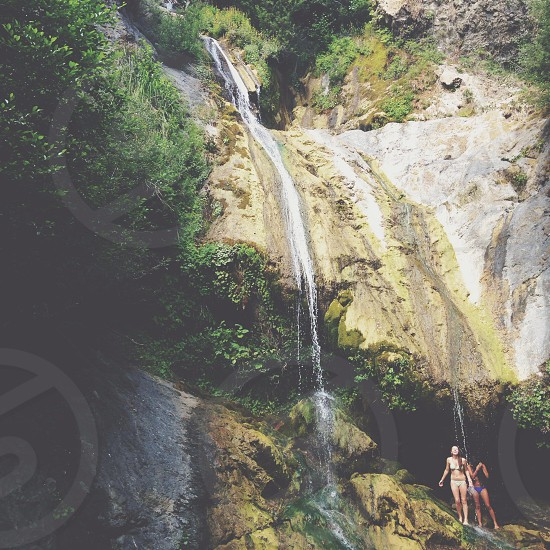 2 women standing near waterfall in bathing suits photo