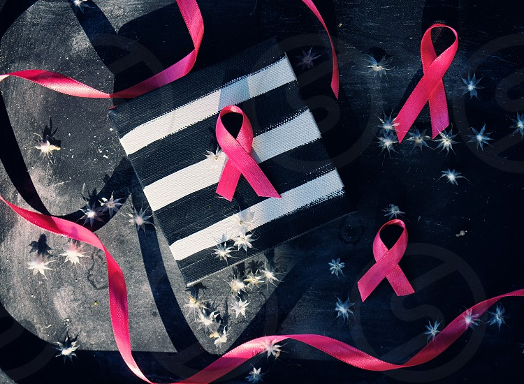 Pink breast cancer awareness ribbons on black background. photo