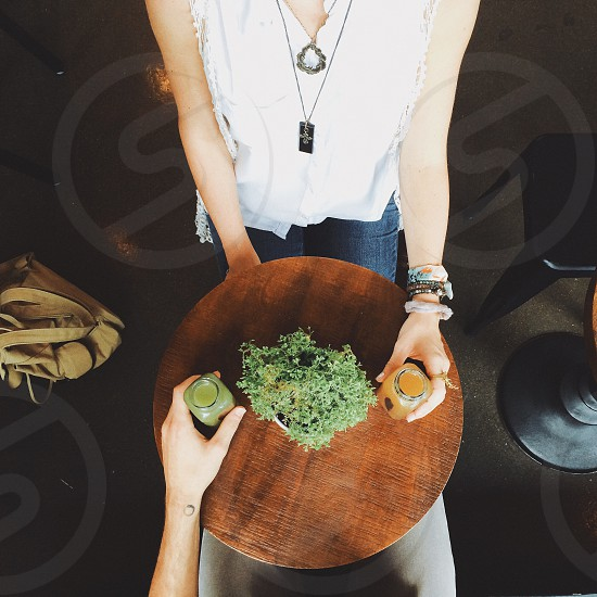 woman in white sleeveless top holding clear glass jar facing person holding glass jar on round coffee table photo