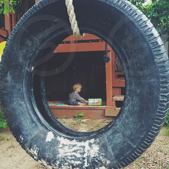 Enjoying the sandbox -tire swing frame photo