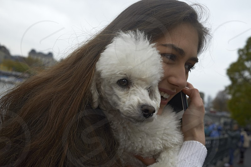 Affluent young woman carrying her white poodle dog under her arm and talking on her mobile phone photo